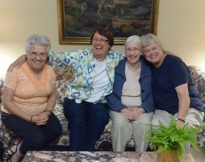A group of smiling sisters sitting together on a sofa.