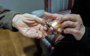 Hands of Sister Bernadette Carlow offering communion to the hand of a hospice patient.