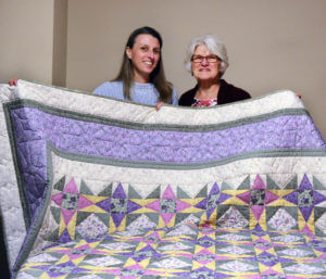Sister Kari Pohl and her mom holding up the hand-stiched purple, pink and yellow quilt that her mom and family made as a raffle item for the Sisters of St. Joseph 55th annual Auxiliary Spring Luncheon Benefit.
