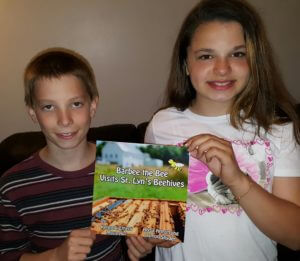 Damon and Alysa, two of four student co-authors, of a book about Sister Lyn and her beehives.