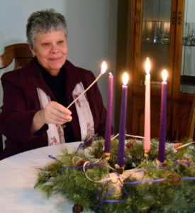 Sister Mary Parks lights candle for fourth week of Advent