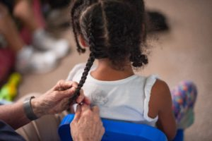 Hands of Sister Lynn Miller braid the hair of a young foster child cared for through the Sisters of St. Joseph Foster Care Program.