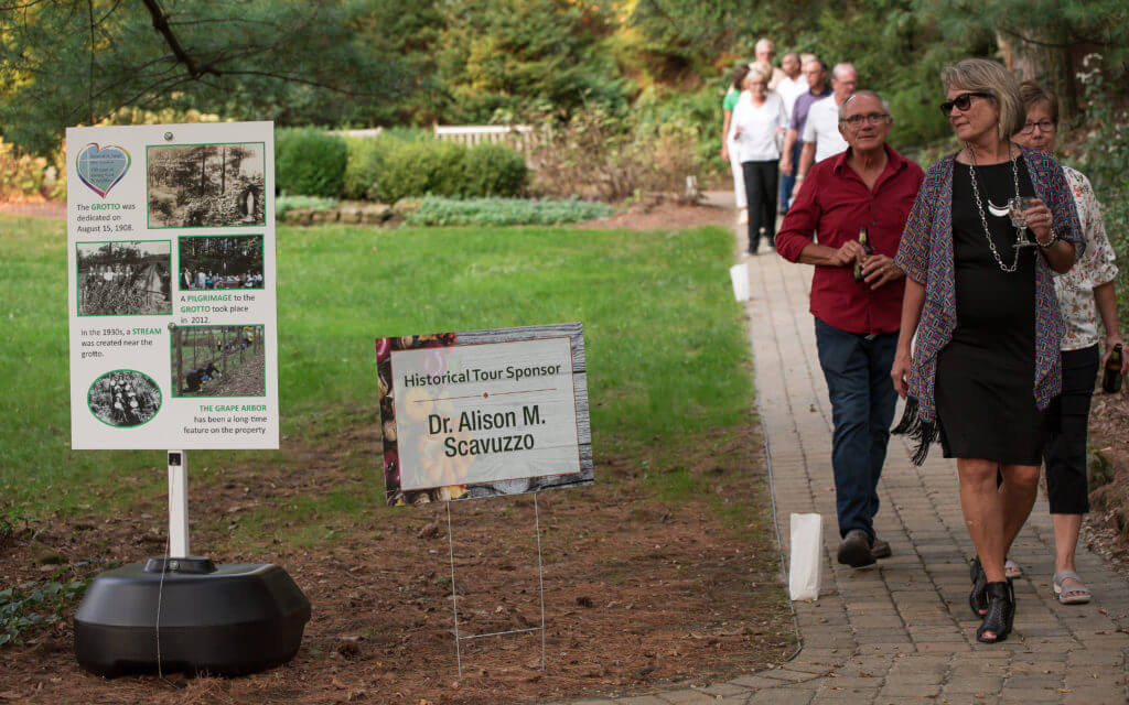 Farm-to-table dinner guests walks down the pathway near the grotto on our grounds.