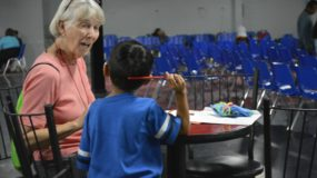 Sister Jeanette Bussen practices English words with a migrant boy at the Humanitarian Respite Center in McAllen, Texas
