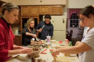 Sister Kari and young adults baking cookies for the incarcerated during a December Nuns and Nones gathering